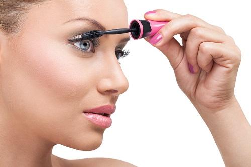 Woman  with long eyelashes and mascara brush