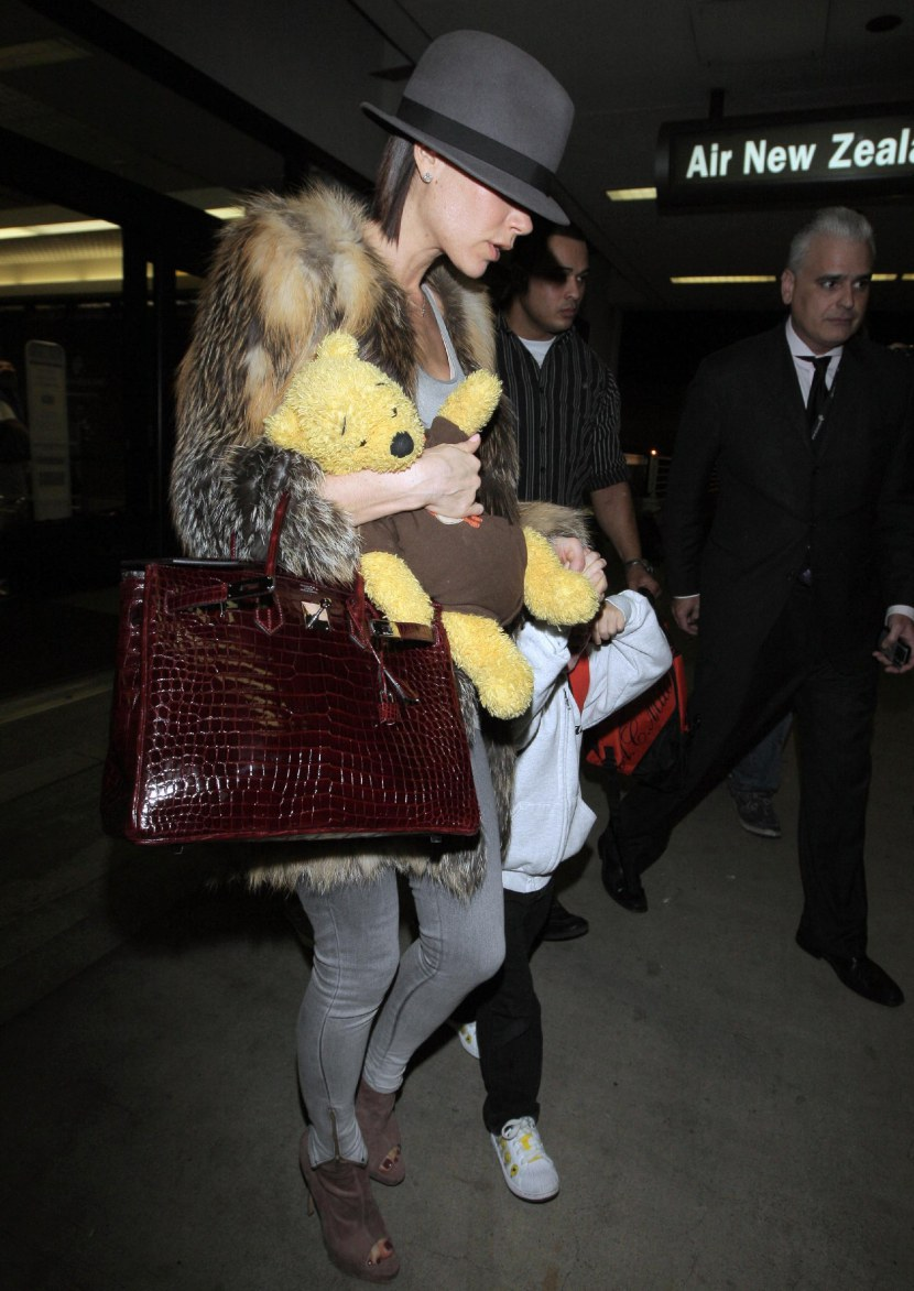 Victoria Beckham arriving at LAX airport on an Air New Zealand flight from London with her three sons, Brooklyn, Romeo and Cruz. Victoria helps tired Cruz by carrying his Winnie the Pooh bear. Los Angeles,  Featuring: Victoria Beckham Where: California, California, United States When: 03 Jan 2010 Credit: WENN
