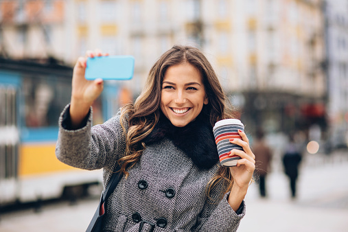 Young woman making selfie on the street